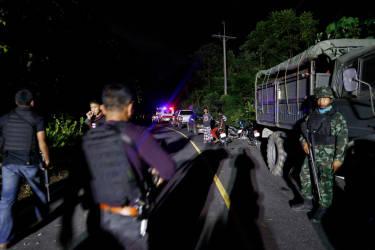 La police, l'armée et les milices sur la scène du meurtre de trois jeunes hommes tués à coups de bâton et dont les cadavres ont été brûlés.