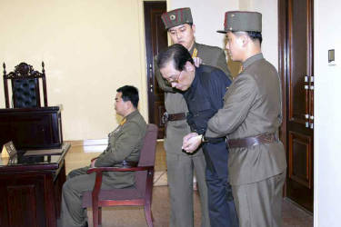 Jang Song Thaek, with his hands tied with a rope, is dragged into the court by uniformed personnel in this December 13, 2013 picture taken from Rodong Sinmun December 12, 2013 and released by Yonhap. North Korea said on Friday that Jang, the uncle of leader Kim Jong Un, previously considered the second most powerful man in the secretive state, has been executed for treason, the biggest upheaval since the death of Kim's father two years ago.    REUTERS/Yonhap  (NORTH KOREA - Tags: POLITICS MILITARY)  ATTENTION EDITORS - THIS PICTURE WAS PROVIDED BY A THIRD PARTY. REUTERS IS UNABLE TO INDEPENDENTLY VERIFY THE AUTHENTICITY, CONTENT, LOCATION OR DATE OF THIS IMAGE. FOR EDITORIAL USE ONLY. NOT FOR SALE FOR MARKETING OR ADVERTISING CAMPAIGNS. NO SALES. NO ARCHIVES. THIS PICTURE IS DISTRIBUTED EXACTLY AS RECEIVED BY REUTERS, AS A SERVICE TO CLIENTS. NO THIRD PARTY SALES. NOT FOR USE BY REUTERS THIRD PARTY DISTRIBUTORS. SOUTH KOREA OUT. NO COMMERCIAL OR EDITORIAL SALES IN SOUTH KOREA