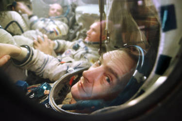 French cosmonaut Jean-Pierre Haignere looks out from the window of Soyuz space craft simulator in Star City, December 10, 1998, during his preparation to international space flight in February 1999. This mission will be the last mission to MIR station.