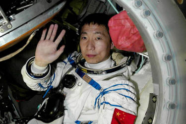 Chinese astronaut Yang Liwei waves before emerging from the Shenzhou V capsule in Inner Mongolia 16 October 2003. China succesfully completed its manned space flight after Yang safely returned to earth.    CHINA OUT AFP PHOTO/XINHUA