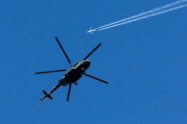 A military helicopter hovers over the mountain cluster as a passenger jet passes by prior to the 2014 Winter Olympics, Tuesday, Feb. 4, 2014, in Krasnaya Polyana, Russia. With militant groups threatening to attack during the next few weeks, security and the safety of competitors and visitors to the coastal area and in the nearby mountains that will host the events has become both heightened and inescapable. (AP Photo/Dmitry Lovetsky)