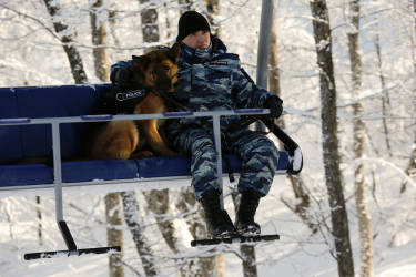 A Russian police officer holds his dog tight as they travel on a ski lift along the Alpine Skiing course of the Sochi 2014 Winter Olympic Games in the Rosa Khutor mountain resort February 2, 2014. Sochi will host the 2014 Winter Olympic Games from February 7 to 23.   REUTERS/Wolfgang Rattay (RUSSIA - Tags: SPORT OLYMPICS SKIING)