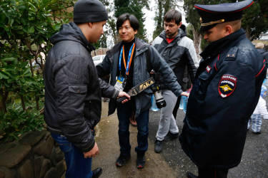 Russian police perform security checks on a journalist at the entrance of church during Orthodox Epiphany celebrations in Sochi January 19, 2014.    REUTERS/Alexander Demianchuk (RUSSIA - Tags: SPORT OLYMPICS MILITARY RELIGION)