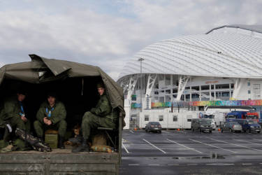 Security personnel sit in the back of a truck outside the Fisht Olympic Stadium at the 2014 Winter Olympics Monday, Jan. 27, 2014, in Sochi, Russia. The Olympics begin Feb. 7th. (AP Photo/David J. Phillip)