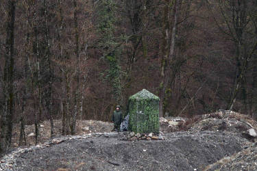 A member of Russia's security forces stands beside their camouflaged tent near the railway track between Krasnaya Polyana and Adler near Sochi, January 29, 2014. Sochi will host the 2014 Winter Olympic Games from February 7 to February 23. REUTERS/Kai Pfaffenbach (RUSSIA - Tags: SPORT OLYMPICS SOCIETY)