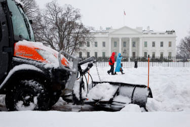 A plow removes snow from the sidewalk in Lafayette Park across the street from the White House in Washington, Thursday, Feb. 13, 2014, as people walk through the snow. After pummeling wide swaths of the South, a winter storm dumped nearly a foot of snow in Washington as it marched Northeast and threatened more power outages, traffic headaches and widespread closures for millions of residents. (AP Photo/Jacquelyn Martin)