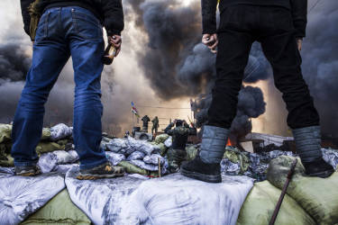 """Anti-government demonstrators stand on barricades during clashes with riot police in Kiev on February 18, 2014. Opposition leader Vitali Klitschko on February 18 urged women and children to leave the opposition's main protest camp on Kiev's Independence Square, known as Maidan, as riot police massed nearby. """"We ask women and children to quit Maidan as we cannot rule out the possibility that they will storm (the camp),"""" the former heavyweight boxing champion told protestors on the square.    AFP PHOTO / SANDRO MADDALENA"""
