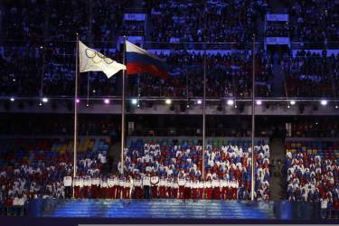 The Olympic flag, left, and the Russian flag, fly during the closing ceremony of the 2014 Winter Olympics, Sunday, Feb. 23, 2014, in Sochi, Russia. (AP Photo/Darron Cummings)