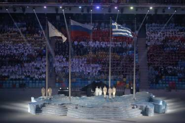 The Greek national flag (R) is raised next to the Olympic flag and Russian national flag at the Closing Ceremony of the Sochi Winter Olympics at the Fisht Olympic Stadium on February 23, 2014.      AFP PHOTO / ADRIAN DENNIS