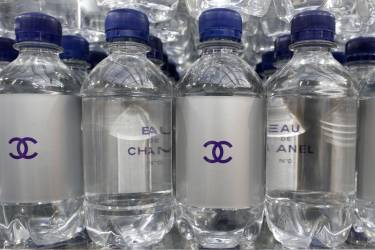 """Chanel mineral bottles are displayed on supermarket shelves at the Grand Palais transformed into a """"Chanel Shopping Center"""" after the German designer Karl Lagerfeld Fall/Winter 2014-2015 women's ready-to-wear collection show for in French fashion house Chanel during Paris Fashion Week March 4, 2014. REUTERS/Benoit Tessier (FRANCE - Tags: FASHION)"""