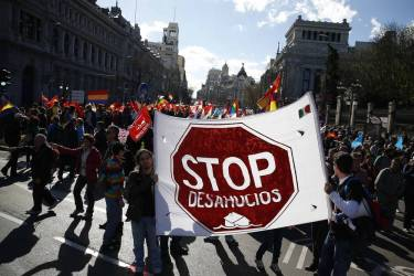 "Anti-austerity demonstrators hold up a sign reading ""Stop Evictions"" as they take part in a demonstration which organisers have labelled the ""Marches of Dignity"" in Madrid, March 22, 2014.Hundreds of thousands of Spaniards rallied in Madrid on Saturday against poverty and EU-imposed austerity in a largely peaceful protest later marred by violent clashes in which police fired rubber bullets. The so-called ""Dignity Marches"" brought hundreds of thousands to the capital, according to estimates of Reuters witnesses. Travelling from all over Spain, they were protesting in support of more than 160 different causes, including jobs, housing, health, education and an end to poverty.   REUTERS/Paul Hanna  (SPAIN - Tags: POLITICS CIVIL UNREST BUSINESS)"