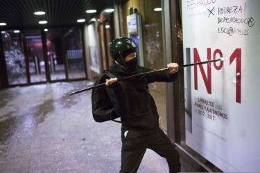 A demonstrator smashes the front of a bank office during a protest against the government in Madrid, Spain, Saturday, March 22, 2014. Spanish police and protesters clashed during an anti-austerity demonstration that drew tens of thousands of people to central Madrid on Saturday. Police said in a statement six officers were injured and 12 people were arrested. (AP Photo/Andres Kudacki)