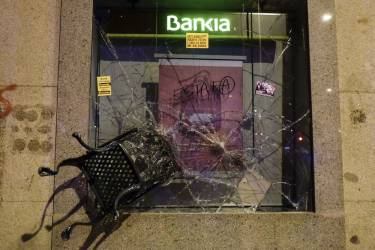 "The destroyed facade of a Bankia's branch is seen during clashes between police and demonstrators at the end of a march dubbed ""the Marches for Dignity 22-M"" to protest against austerity in Madrid on March 22, 2014. Eight ""columns"" of demonstrators, who have traveled from Andalusia, Catalonia, Asturias or Extremadura and other Spanish regions in an attempt to highlight the plight of struggling Spaniards, converged on Madrid today for a mass protest.   AFP PHOTO/ PEDRO ARMESTRE"