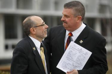 Frank Colasonti Jr (L) and James Barclay Ryder, who have been together 26 years, hold their marriage license outside the Oakland County courthouse after being married by County Clerk Lisa Brown in Pontiac, Michigan March 22, 2014. Michigan's ban on same-sex marriage violates the U.S. Constitution and must be overturned, a federal judge ruled on Friday.    REUTERS/Rebecca Cook (UNITED STATES - Tags: POLITICS SOCIETY)