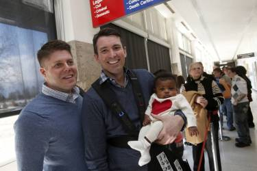 Jim Schaffer (L) and his partner Jason McIntosh stand in line with their adopted baby Norah as they wait in line for a marriage license at the Oakland County Courthouse, after a Michigan federal judge ruled a ban on same-sex marriage violates the U.S. Constitution and must be overturnedn in Pontiac, Michigan March 22, 2014.   REUTERS/Rebecca Cook (UNITED STATES - Tags: POLITICS RELIGION SOCIETY)