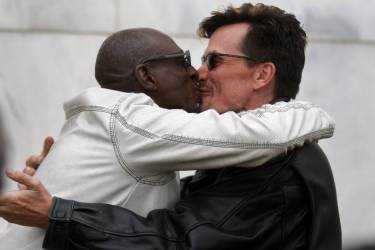 Newly married Roland Smith (L) and Paul Mattson kiss each other after their brief wedding ceremony outside the Oakland County Courthouse after a Michigan federal judge ruled a ban on same-sex marriage violates the U.S. Constitution and must be overturned in Pontiac, Michigan March 22, 2014.   REUTERS/Rebecca Cook (UNITED STATES - Tags: POLITICS RELIGION SOCIETY)