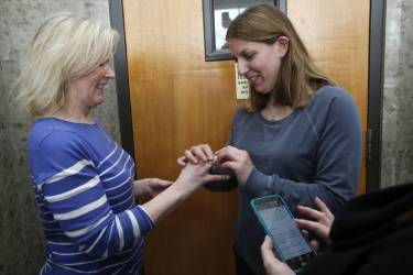 Two women exchange rings during their wedding ceremony in the hallway of the Oakland County Courthouse as the woman officiating the wedding reads the marriage vows from her cell phone, after a Michigan federal judge ruled a ban on same-sex marriage violates the U.S. Constitution and must be overturned in Pontiac, Michigan March 22, 2014.   REUTERS/Rebecca Cook (UNITED STATES - Tags: POLITICS RELIGION SOCIETY)