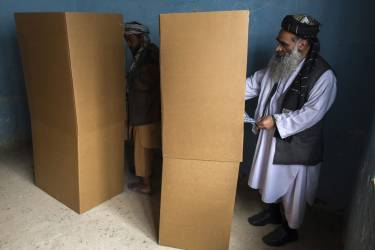 Afghan men vote at a polling station in Mazar-i-sharif  April 5,2014. Voting was largely peaceful in Afghanistan's presidential election on Saturday, with only isolated attacks on polling stations as a country racked by decades of chaos embarked on its first ever democratic transfer of power. REUTERS/Zohra Bensemra (AFGHANISTAN - Tags: POLITICS ELECTIONS)