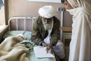 March 30, 2014 - Kandahar, Afghanistan - Mirwais Hospital sponsored by the Red Cross.The father of Noruhuda, a five-year-old boy wounded by shrapnel in a crossfire between Afghan National Army and Taliban insurgents, shows a relative bits of shrapnel from a mortar that wounded his son.