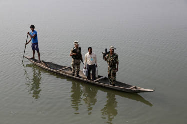A polling officer carrying electronic voting machines accompanied by two securitymen arrives in a country boat on the eve of parliamentary elections at Misamora Sapori, an island in the River Brahmaputra in Assam state, India, Sunday, April 6, 2014. India will hold national elections from April 7 to May 12, kicking off a vote that many observers see as the most important election in more than 30 years in the world's largest democracy. (AP Photo/Anupam Nath)