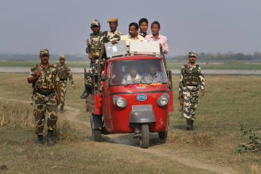 A polling officer carrying electronic voting machines arrives accompanied by security men in a three wheeler on the eve of parliamentary elections at Misamora Sapori, an island in the River Brahmaputra in Assam state, India, Sunday, April 6, 2014. India will hold national elections from April 7 to May 12, kicking off a vote that many observers see as the most important election in more than 30 years in the world's largest democracy. (AP Photo/Anupam Nath)