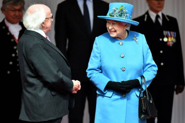 Britain's Queen Elizabeth II greets Irish President Michael D. Higgins (L) during the ceremonial welcome at the Royal Dais in Windsor, west of London on April 8, 2014. Ireland's Michael D. Higgins is making the first state visit by a president of the republic since it gained independence from neighbouring Britain. The visit comes three years after Queen Elizabeth II made a groundbreaking trip to the republic, which helped to heal deep-rooted unease and put British-Irish relations on a new footing. Higgins' return visit will be seen as an official sign of further progress following the hard-won peace in Northern Ireland, which remains part of the United Kingdom. AFP PHOTO / POOL / BEN STANSALL