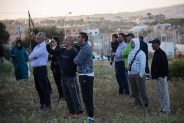 A Melilla, le 24 avril. Une centaine de migrants se sont ruŽs sur la barrire qui sŽpare le Maroc de l'enclave espagnole. Pendant l'assaut, quelques-uns ont pu passer c™tŽ espagnol, d'autres se sont retrouvŽs coincŽs, plusieurs heures durant, sur la barrire.Les badauds regardent la scne© Olivier JOBARD / M.Y.O.P.