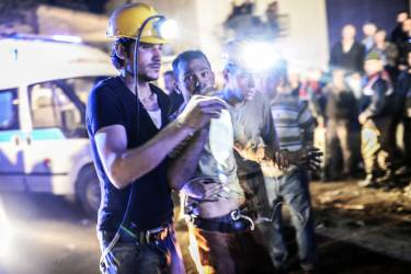 """A miner came out helped by friends after an explosion in Manisa on May 13, 2014. Four miner were killed and as many as 300 trapped after a mine collapse in the western Turkish city of Manisa, a local official said. """"At least 200-300 workers were working in the mine when an electric fault caused an explosion,"""" the mayor of Soma, a district of Manisa, told private NTV television. AFP PHOTO/BULENT KILIC"""