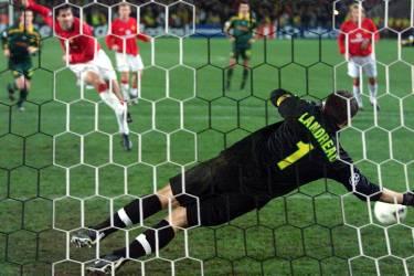 le joueur de Manchester United, Ruud Van Nistelrooy (G), tire et marque le penalty face au gardien nantais Mickael Landreau (D), le 20 février 2002 sur la pelouse du stade de la Beaujoire à Nantes, lors du match Nantes/Manchester United comptant pour le deuxième tour de la Ligue des Champions de football.   AFP PHOTO VALERY HACHE   Manchester United 's Ruud Van Nistelrooy (L) scores a penalty kick for his team as Nantes ' goalkeeper Mickael Landreau jumps in vain, during the UEFA Champions League game Nantes vs Manchester United at Stade de La Beaujoire in Nantes, 20 February 2002. Both teams finished in a draw 1-1. Other players are unidentified.