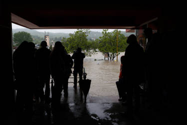 Bosnian people look out over the river Bosna which flooded a bridge in town of Zavidovici 120 kms north of Sarajevo, Thursday May 15, 2014. Heavy rainfall caused the river Bosna to flood surrounding areas causing power cuts and road blockades in some suburban and rural areas. (AP Photo/Amel Emric)