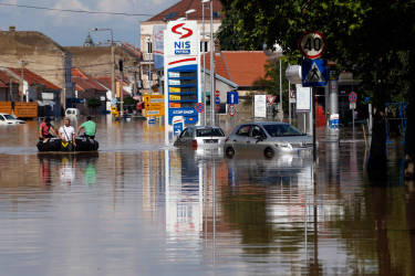 People paddle a boat down a flooded street in Obrenovac, some 30 kilometers (18 miles) southwest of Belgrade, Serbia, Sunday, May 18, 2014. In Serbia, more than 20,000 people have been forced from their homes. Officials there fear more flooding later Sunday as floodwaters travel down the Sava and reach the country. Serbian officials said that the flood wave might be lower than initially expected, because the river broke barriers upstream in Croatia and Bosnia. Experts said they expect Sava floodwaters to rise for two more days, then subside. (AP Photo/Darko Vojinovic)