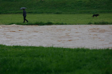 A man walks along a flooded field in a suburb of Sarajevo on Wednesday, May 14, 2014. Heavy rainfall caused the river Bosna to flood surrounding areas causing power cuts and road blockades in some suburban and rural areas. (AP Photo/Amel Emric)