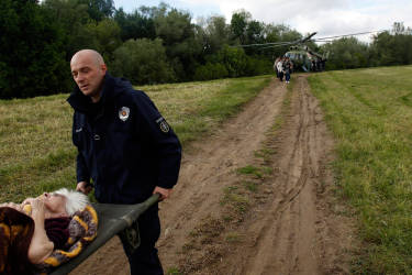 Serbian police officers carry an old woman out of military helicopter during flood evacuation from Obrenovac, some 30 kilometers (18 miles) southwest of Belgrade Serbia, Saturday, May 17, 2014. Record flooding in the Balkans leaves at least 20 people dead in Serbia and Bosnia and is forcing tens of thousands to flee their homes. Meteorologists say the flooding is the worst since records began 120 years ago. (AP Photo/Darko Vojinovic)