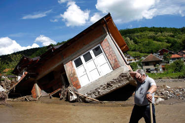 A man reacts near a house tilted by floods in the village of Krupanj, west from Belgrade, May 19, 2014. Communities in Serbia and Bosnia battled to protect towns and power plants on Monday from rising flood waters and landslides that have devastated swathes of both countries and killed dozens of people. REUTERS/Marko Djurica (SERBIA - Tags: DISASTER ENVIRONMENT TPX IMAGES OF THE DAY)
