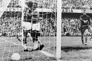 Brazilian forward Pele (C) congratulates his teammate Vava (20) after he scored a goal as Swedish goalkeeper Karl Svensson reacts 29 June 1958 in Stockholm during the World Cup final between Brazil and Sweden. Vava and Pele scored two goals each as Brazil won its first title beating World Cup host Sweden 5-2. AFP PHOTO