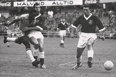 17-year-old Brazilian forward Pele (L) kicks the ball past two Welsh defenders during the World Cup quarterfinal soccer match between Brazil and Wales 19 June 1958 in Goteborg. Pele scored the only goal of the match to help Brazil advance to the semifinals.  