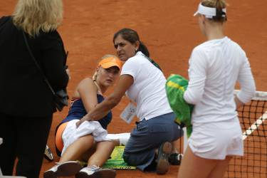 France's Kristina Mladenovic, second left on the clay, receives medical assistance as she plays Alison Riske, of the U.S, right, during their second round match of  the French Open tennis tournament at the Roland Garros stadium, in Paris, France, Thursday, May 29, 2014. (AP Photo/Michel Euler)