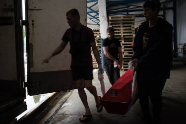 Activists put the coffin with the body one of 31 Russian citizens inside of a refrigerator truck which was prepared to bring the bring the bodies to Russia.