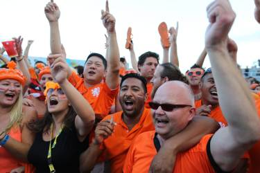 Soccer fans celebrate a goal scored by the Netherlands during a live broadcast of the World Cup match with Spain, inside the FIFA Fan Fest area on Copacabana beach in Rio de Janeiro, Brazil, Friday, June 13, 2014. The Netherlands thrashed Spain 5-1 Friday. It was a humiliating defeat for the defending champions. (AP Photo/Leo Correa)