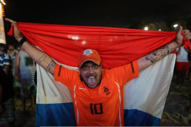A soccer fan holding a Dutch national flag poses for a photo after watching the live broadcast of the World Cup match between Spain and the Netherlands, inside the FIFA Fan Fest area on Copacabana beach in Rio de Janeiro, Brazil, Friday, June 13, 2014. The Netherlands thrashed Spain 5-1 Friday. It was a humiliating defeat for the defending World Cup champions. (AP Photo/Leo Correa)