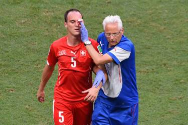 Switzerland's defender Steve von Bergen (L) receives medical assistance after being injured  during a Group E football match between Switzerland and France at the Fonte Nova Arena in Salvador during the 2014 FIFA World Cup on June 20, 2014.    AFP PHOTO / DIMITAR DILKOFF