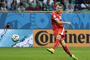 Switzerland's Granit Xhaka kicks his side's second goal during the group E World Cup soccer match between Switzerland and France at the Arena Fonte Nova in Salvador, Brazil, Friday, June 20, 2014. (AP Photo/Natacha Pisarenko)