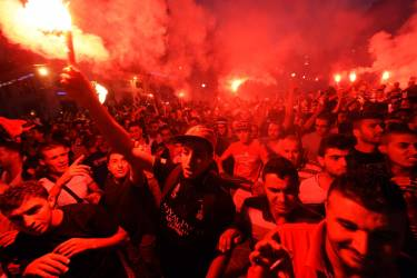 Algeria's fans celebrate and hold flares as they watch the FIFA 2014 World Cup football match Algeria vs South Korea in Algiers, on June 22, 2014. AFP PHOTO/FAROUK BATICHE