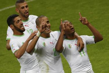 Algeria's national soccer players celebrate their team's fourth goal by Yacine Brahimi (R) during their 2014 World Cup Group H soccer match at the Beira Rio stadium in Porto Alegre June 22, 2014.  Pictured are: (counter clockwise from top) Algeria's Islam Slimani, Rafik Halliche, Madjid Bougherra and Yacine Brahimi. REUTERS/Marko Djurica (BRAZIL  - Tags: SOCCER SPORT WORLD CUP)       TOPCUP
