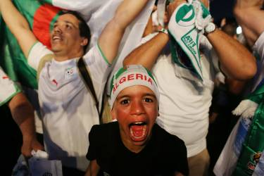 An Algeria young soccer fan celebrates his team's victory after a live broadcast of the group H World Cup match between Korea and Algeria, inside the FIFA Fan Fest area on Copacabana beach, in Rio de Janeiro, Brazil, Sunday, June 22, 2014. (AP Photo/Leo Correa)
