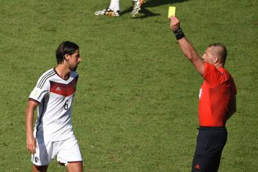 Argentinian referee Nestor Fabian Pitana shows the yellow card to Germany's midfielder Sami Khedira, during a quarter-final football match between France and Germany at the Maracana Stadium in Rio de Janeiro during the 2014 FIFA World Cup on July 4, 2014.  AFP PHOTO / CHRISTOPHE SIMON