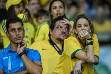 Fans of Brazil gesture during the Brazil 2014 FIFA World Cup semifinal match Brazil vs Germany, outside the Mineirao Stadium in Belo Horizonte, on July 8, 2014.      AFP PHOTO / GUSTAVO ANDRADE