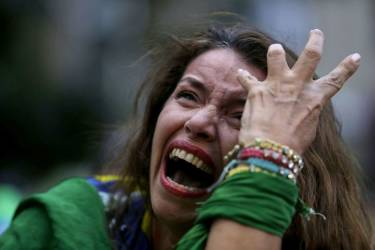 A Brazil soccer fan cries as Germany scores against her team at a semifinal World Cup match as she watches the game on a live telecast in Belo Horizonte, Brazil, Tuesday, July 8, 2014. (AP Photo/Bruno Magalhaes)
