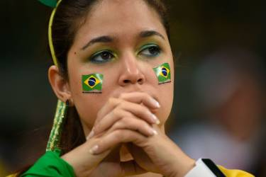 A fan of Brazil reacts during the semi-final football match between Brazil and Germany at The Mineirao Stadium in Belo Horizonte during the 2014 FIFA World Cup on July 8, 2014.  AFP PHOTO / FABRICE COFFRINI