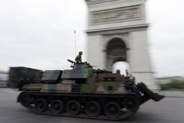 French soldiers drive an armoured vehicle past the Arc de Triomphe on the Place de L'Etoile prior to the start of the annual Bastille Day military parade on the in Paris, on July 14, 2014. AFP PHOTO / KENZO TRIBOUILLARD